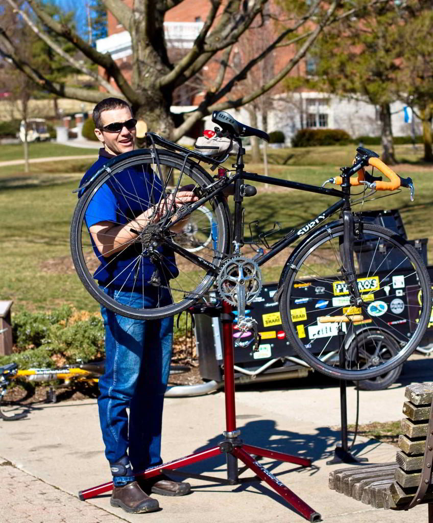 Ben Wyse, owner of Wyse Cycles, works on a bike at his mobile repair station.