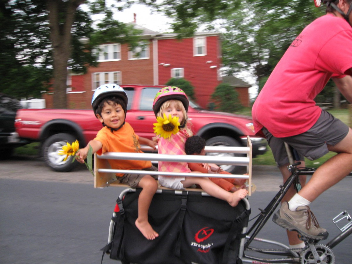 A family with two kids ride together on an Xtracycle bicycle.